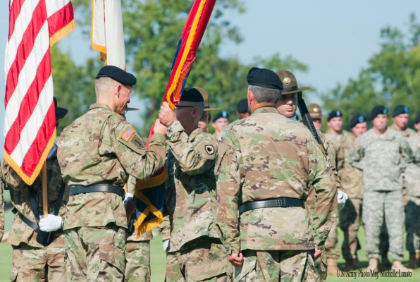 Brig. Gen. Miles Davis, commander of the 98th Training Division (Initial Entry Training), passes the division colors to Command Sgt. Maj. Todd Priest, division command sergeant major, during an assumption of command ceremony on September 11 at the National Infantry Museum at Fort Benning, Georgia. The 98th Training Division is an Army Reserve unit headquarterd at Fort Benning and is one of two divisions that provide drill sergeants who help mold future Soldiers.