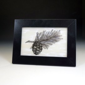 Pine design in black, on patterned clear glass in a frame
