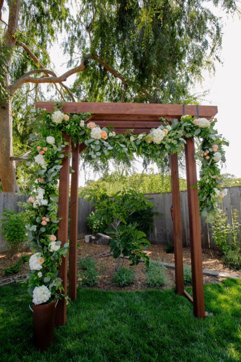 flower decorated arbor for a backyard wedding