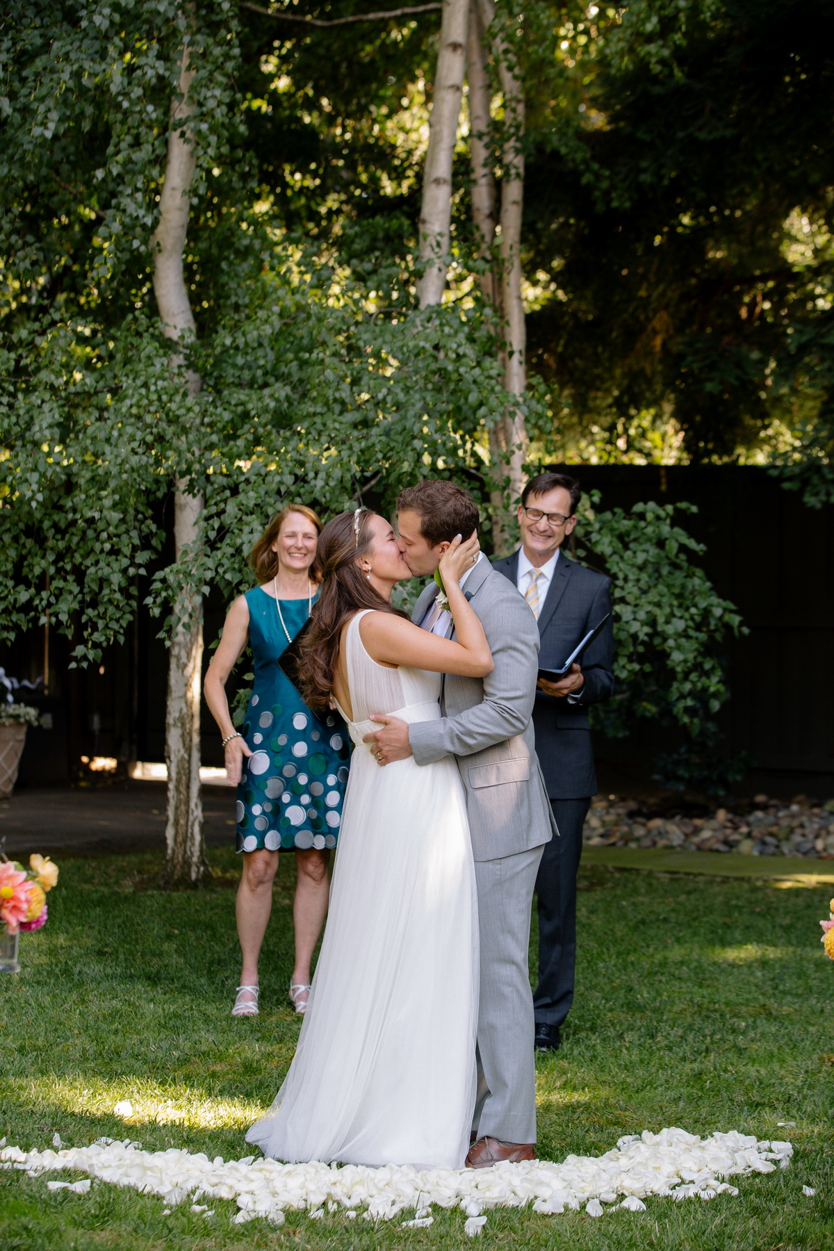 bride and groom kiss during their backyard wedding ceremony