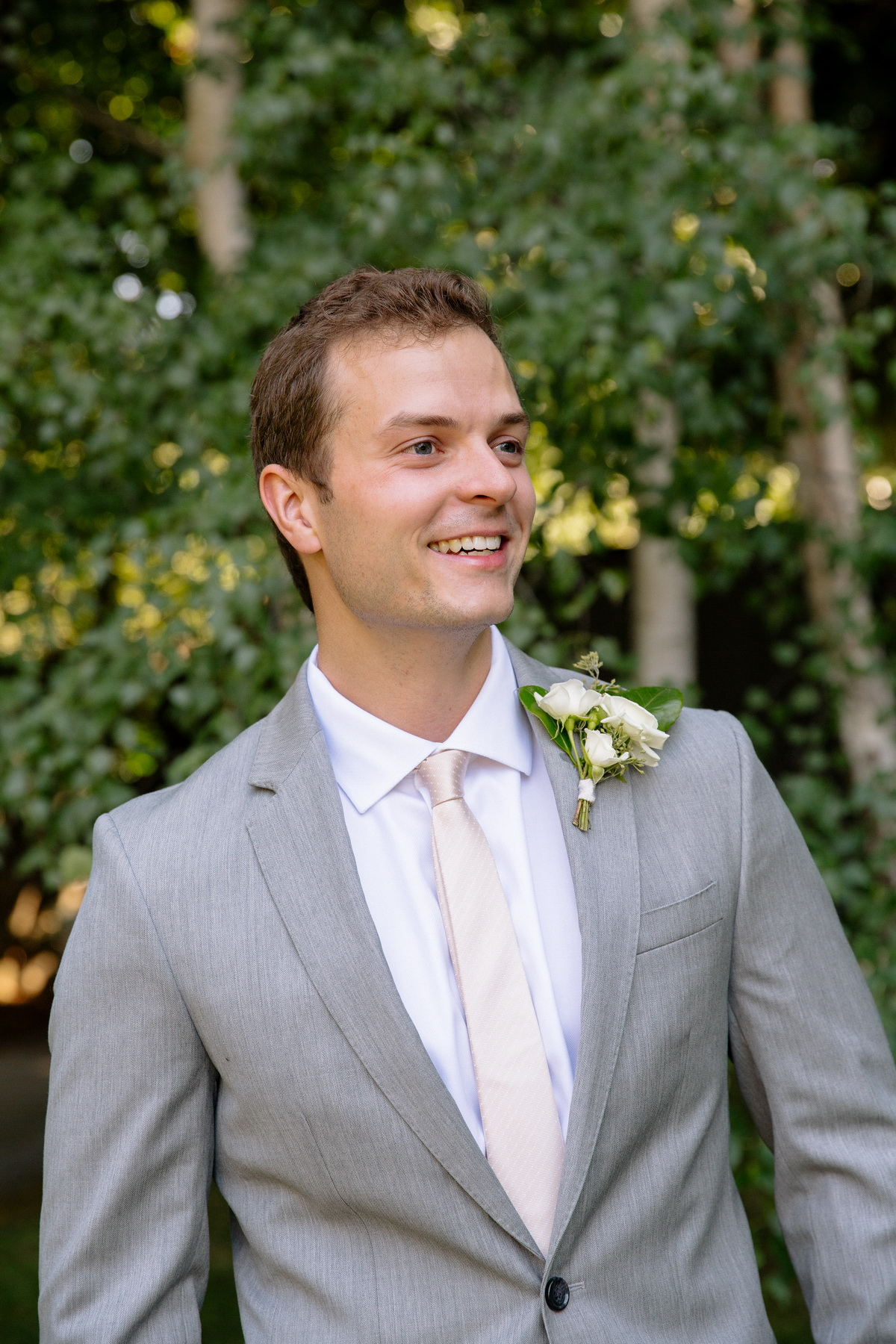 casual portrait of a groom in a grey suit