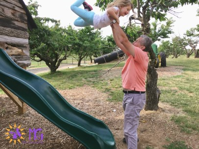 little girl getting swung into the air by her grandpa