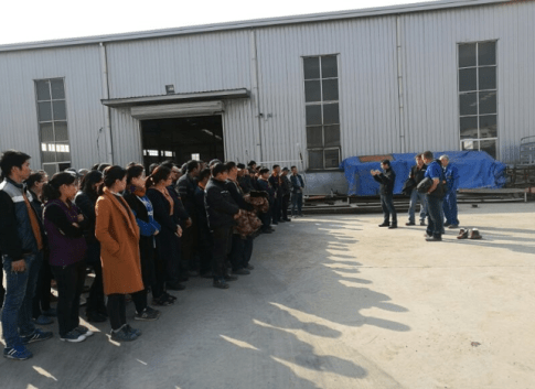 Staff meeting in front of the factory.