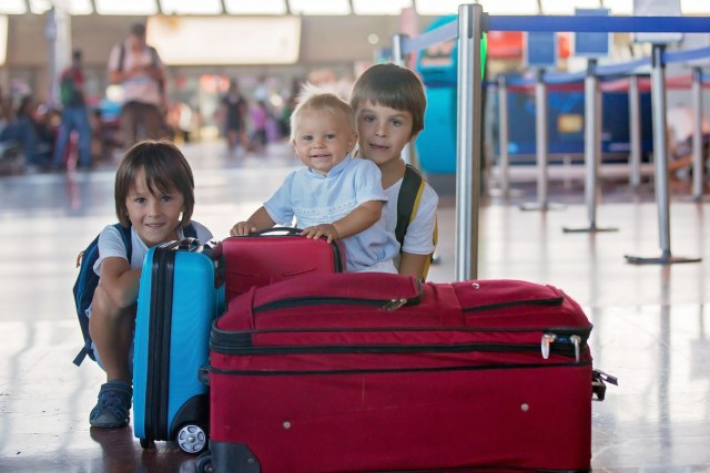 Children, traveling together, waiting at the airport for boarding
