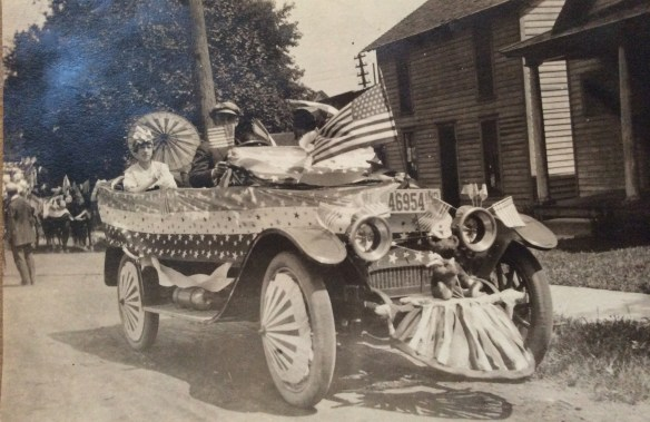 John Grover Fleck and passengers (names?) preparing for July 4, 1915 parade in Hobart, Indiana. Note the teddy bear holding the flag below the license plate.