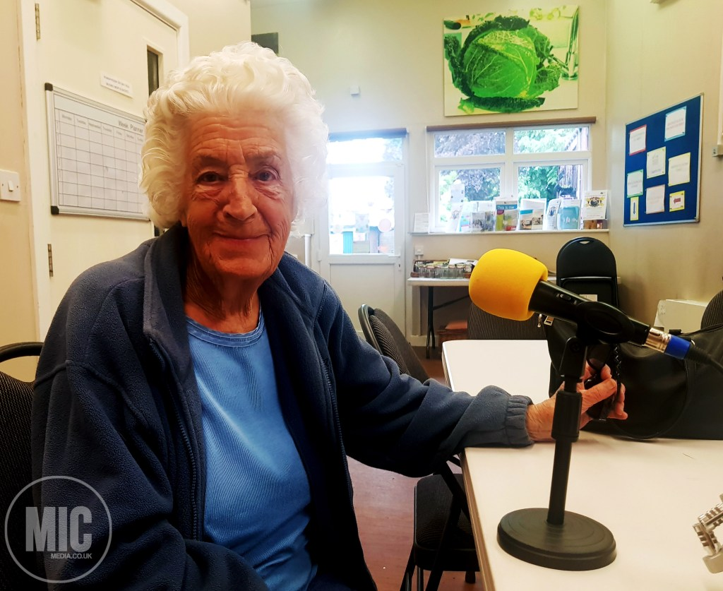 a photo of a women with white hair and a blue tshirt. she is sat on a chair. we can see her from the waist up. the3 table in front of her has a microphone with a yellow foam end on it. The microphone is pointed towards the lady