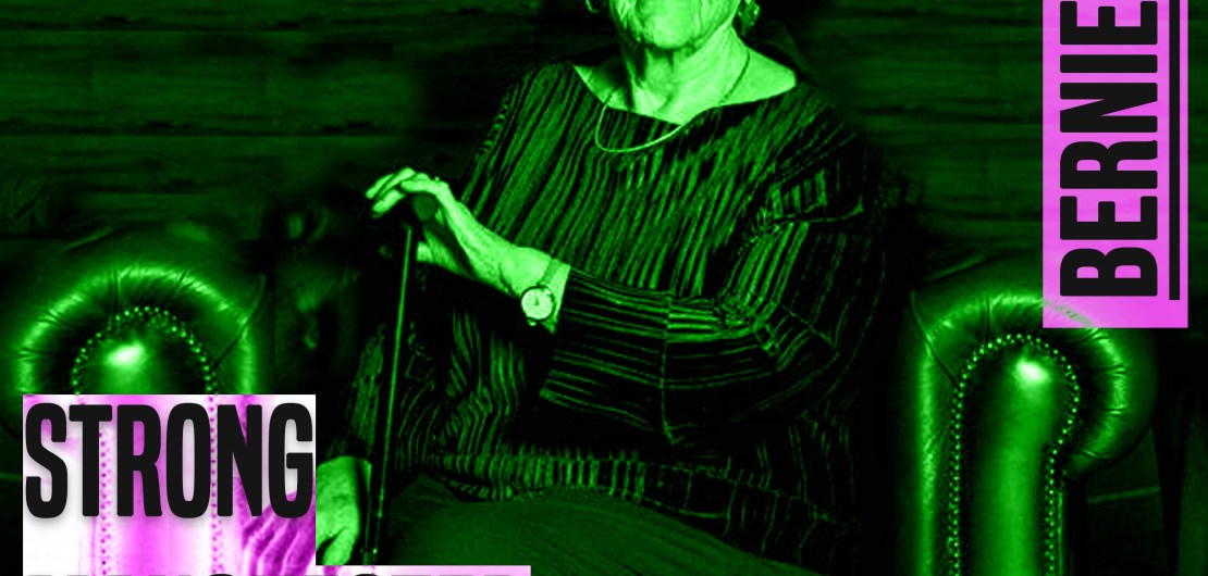 A photo of women sat in a leather Chesterfield style chair. The image is from her knees up. She is holding a walking stick. She is white. she is looking directly at the camera. She is wearing dark clothes. She has short white hair. The image has a green hue to it. to the left of her knees are the words 'strong manchester women' in grey lettering and a thick font in capital letters. In the same style font, next to her right ear are the words 'Bernie Wood'.