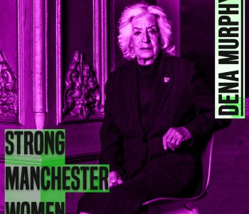 A woman with white hair sits on a chair and looks at the camera. Her right elbow leans on the back of the chair. She has her legs crossed. She is wearing a dark skirt and jacket. The photo crops just under her knees. The picture has a purple hue to it. On the leff of the picture are the words 'strong manchester women' on the right 'Dena Murphy' - both in capital and grey colour letters