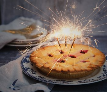 A photo of a pie with sparklers in it
