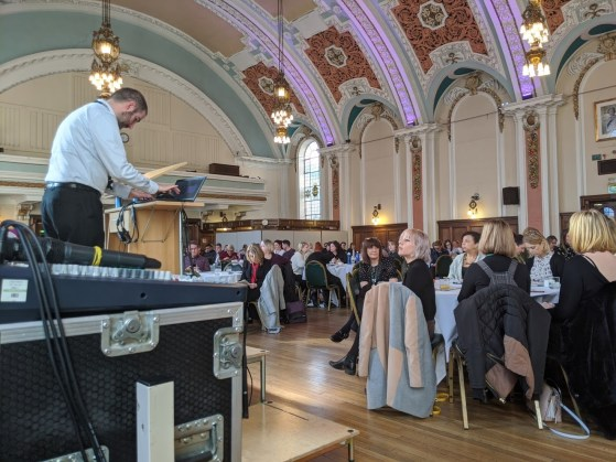 a photo of a room full of people sat at tables. The ceiling of the room is ornate and a mam stands at a lectern at the front of the room.