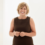 a woman with a black dress and short blonde hair smiles
