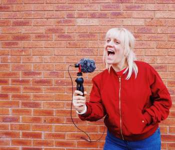 a women is standing in fron tof a brick wall, she is holding a microphone and speaking into it. she has a red coat on a and medium length blonde hair