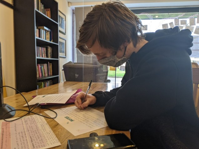 Image of young man in black jumper with a grey face mask on filling in script notes.