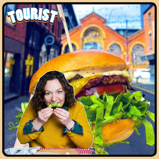 [Image of a town blurred out in the background and a large burger in the centre of the background with the podcast guest Jessica Fostekew on the left wearing a yellow knitted jumper and biting into a piece of food.]