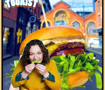 Image of a town blurred out in the background and a large burger in the centre of the background with the podcast guest Jessica Fostekew on the left wearing a yellow knitted jumper and biting into a piece of food.