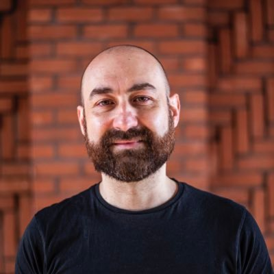 an image of a man facing straight on. He is smiling. He has a beard and a shaved head hairstyle