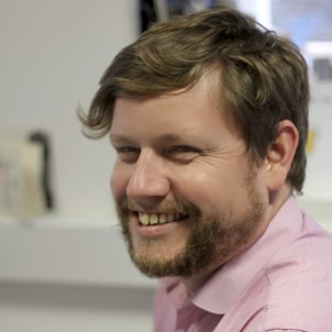 a headshot of a man with a beard, siling. He has a pink shirt on