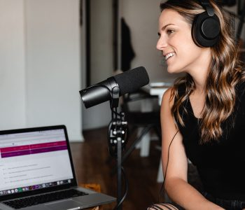 Image of a woman with headphones on and black vest top and microphone with a laptop in the background