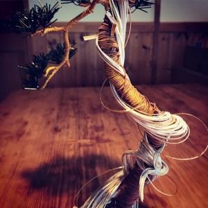 水引アート。動きのある松の幹にある白い部分は、落雷などで枯れ一部風化した部分、盆栽でいう神(じん)や舎利(しゃり)を表現したもの。