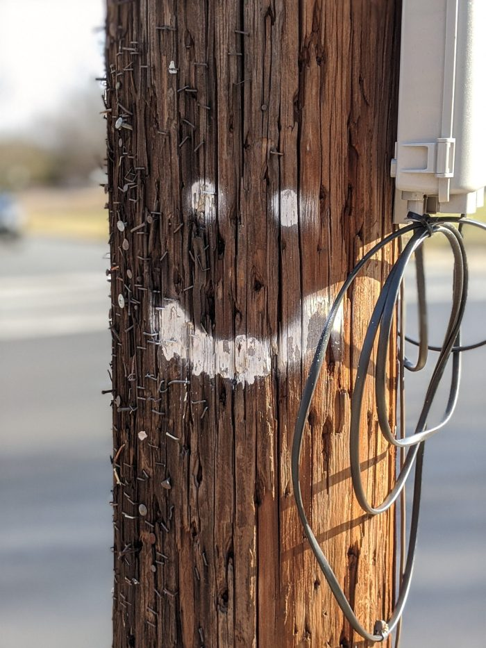 Telephone poll with smiley face spray painted on.