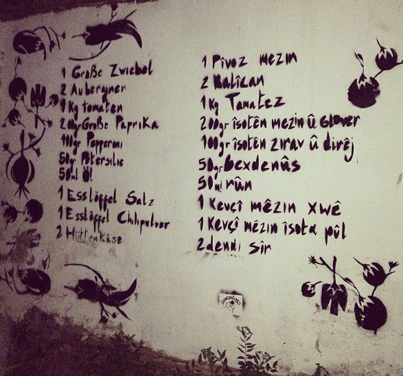 Recipe for a soup, in Turkish and in German, in front of an open community garden which grows all the required veggies.