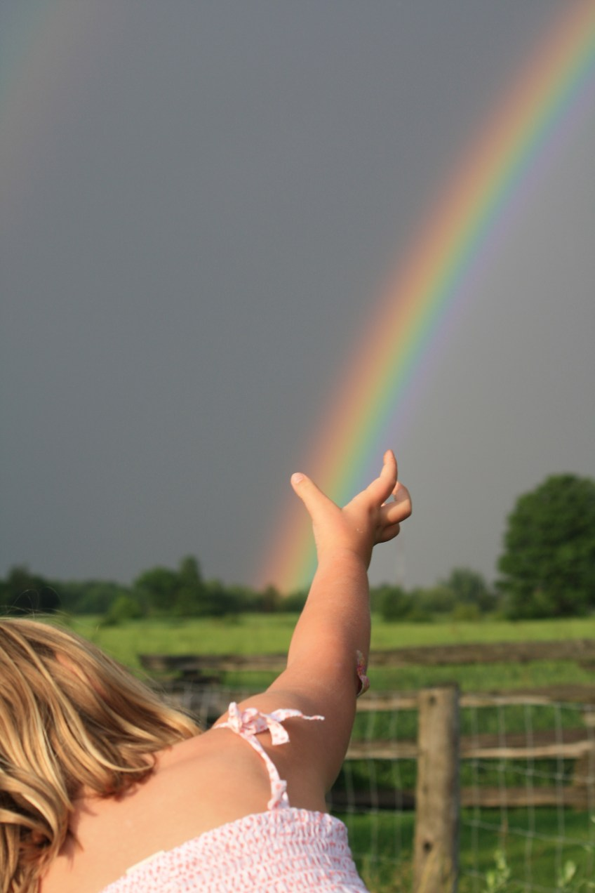 child reaching for a rainbow
