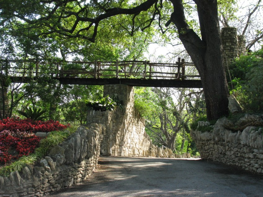 a path surrounded by tall trees, with a bridge overhead
