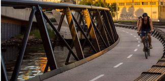 People riding bikes on Jim Stynes Bridge