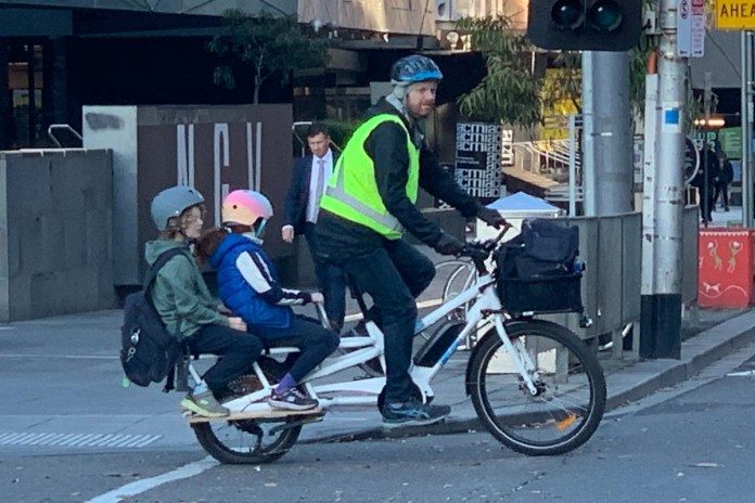 Man and two children riding e-bike
