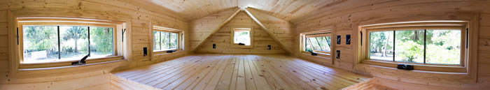 An example of a loft with a gable roof with dormer windows for increased head room - Tinier Living by Tiny House Builders