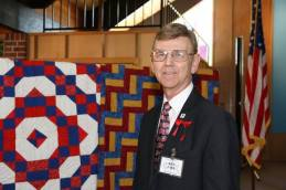 Mr. Ken Faba, U. S. Army, Helicopter Pilot, Vietnam, 1965-66, stands before some of the beautiful Quilts of Valor.