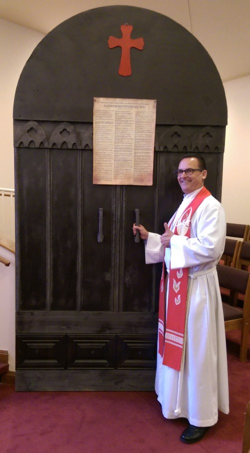 Pastor Reuter at a replica of the famous door