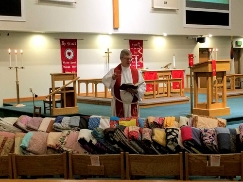 Emmanuel Lutheran pastor blesses quilts for Care-Van 2019