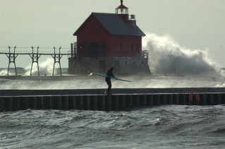 Waves crash into the south pier as a surfer gets ready to jump into the water.