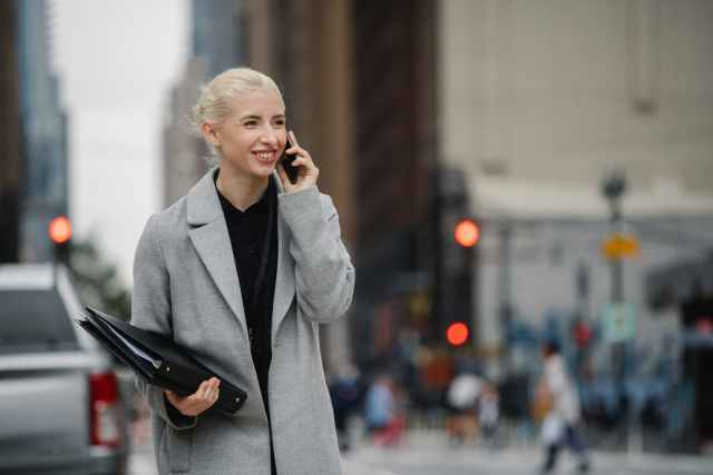 cheerful businesswoman talking on smartphone in town