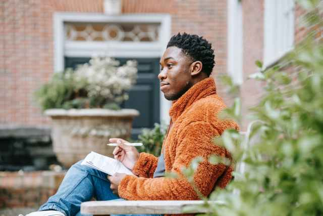pensive black man studying on street
