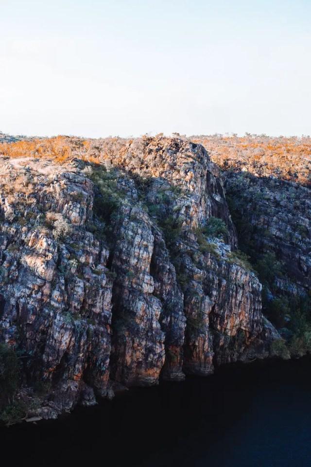 rocky cliff near calm river in peaceful nature