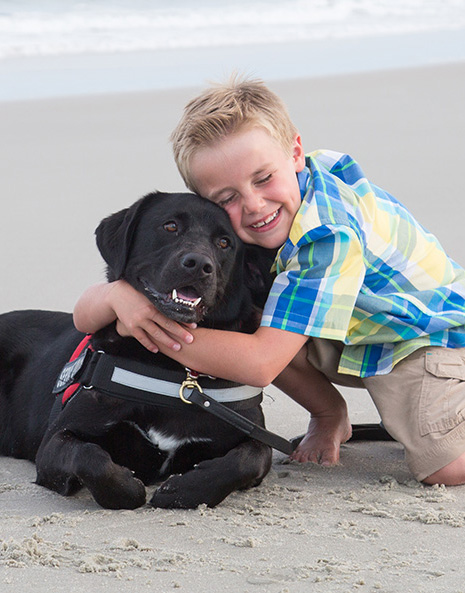 Myrtle Beach Photography - Young boy hugging black labardor dog