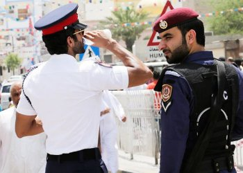 A Bahraini police officer takes a drink of water while standing with a riot policeman outside of a shiite mosque in Manama, Bahrain/AP