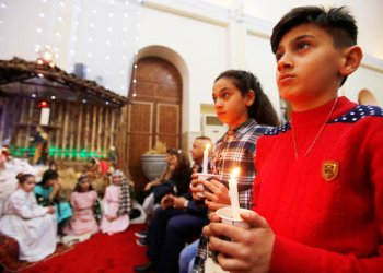 Iraqi Christians children cary candles during a mass on Christmas eve at St.George Chaldean Church in Baghdad, Iraq/REUTERS