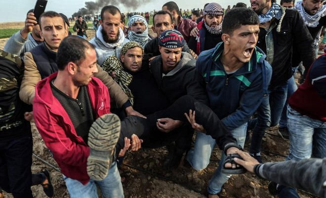 Palestinian protesters carry a wounded comrade during clashes with Israeli forces near the Israel-Gaza border east of the southern Gaza strip city of Khan Yunis/AFP
