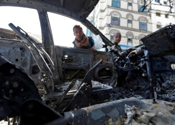Yemeni boys peer inside the husk of a burnt car as they inspect damage from recent clashes between Huthi rebel fighters and loyalists of Yemen's slain ex-president Ali Abdullah Saleh in the capital Sanaa on December 6, 2017 Mohammed HUWAIS (AFP)