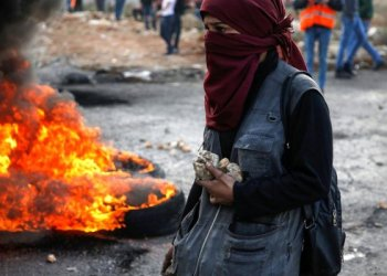 A Palestinian protester holds stone during clashes with Israeli forces north of Ramallah in the Israeli-ocupied West Bank/AFP