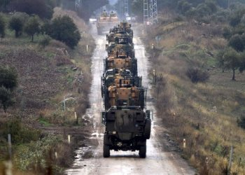 A convoy of Turkish Army armoured personnel carriers led by a tank are driven toward the border with Syria, in the outsikirt of Hassa,Turkey/AP