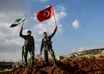 Ankara-backed Syrian rebel fighters hold up Turkish and Free Syrian Army flags on a road leading to Afrin. / AFP/File / Ozan KOSE