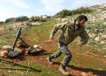 A Turkish-backed Syrian rebel fighter runs after firing a mortar shell towards Kurdish forces from the People's Protection Units (YPG) in the Afrin region on Monday. / AFP / OMAR HAJ KADOUR