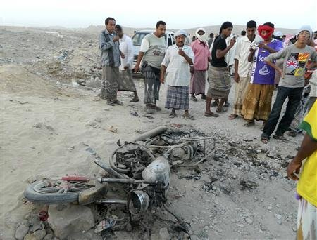 people gather around around a motorcycle destroyed in a drone strike in Yemen /Reuters