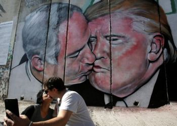 Tourists kiss each other as they stand in front of a mural depicting Donald Trump and Benjamin Netanyahu kissing in the West Bank city of Bethlehem October 29, 2017. / REUTERS / Mussa Qawasma