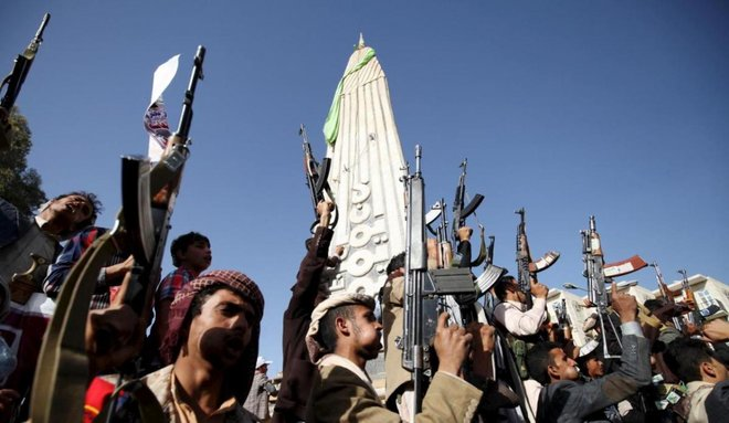 File photo showing Houthi militants raising their weapons in defiance of a UN arms embargo, Apr 16, 2015. (Reuters)