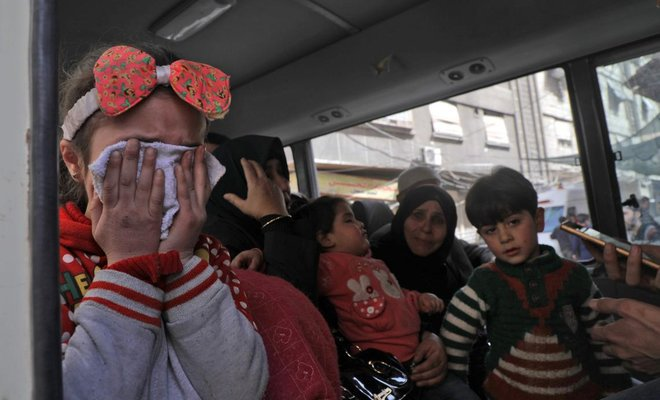 Children wait to be evacuated from Douma, Eastern Ghouta, in Syrian Red Crescent buses on the eastern outskirts of the capital Damascus on March 19, 2018. (AFP)